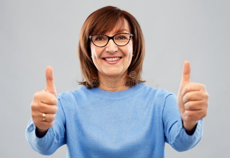Stående av den höga kvinnan som visar upp tummar arkivfoto