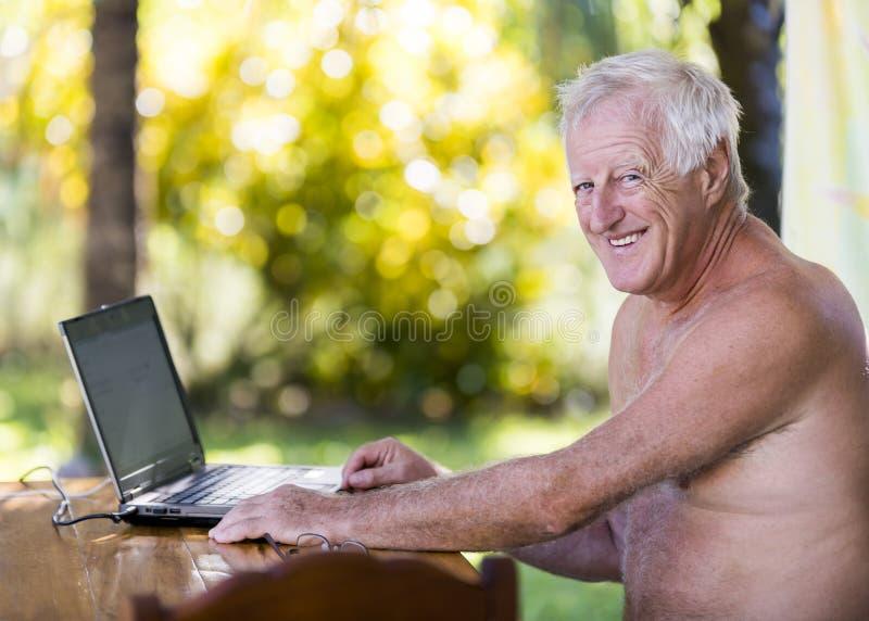 Stående av den höga mannen som arbetar med bärbara datorn i utomhus- utan skjortan royaltyfria bilder