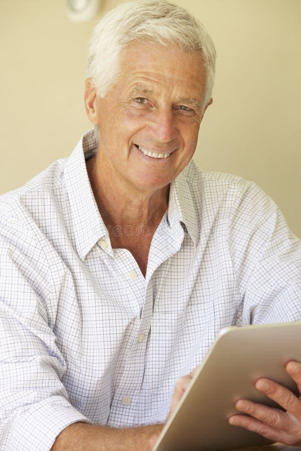 Stående av den höga mannen som hemma använder den Digital minnestavlan arkivfoto