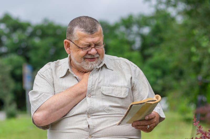 Stående av den höga mannen som läser en intressant bok royaltyfria bilder