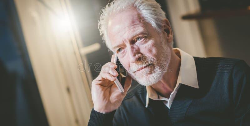 Stående av den höga moderna mannen som talar på mobiltelefonen royaltyfria foton