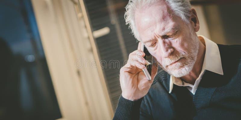 Stående av den höga moderna mannen som talar på mobiltelefonen royaltyfria bilder