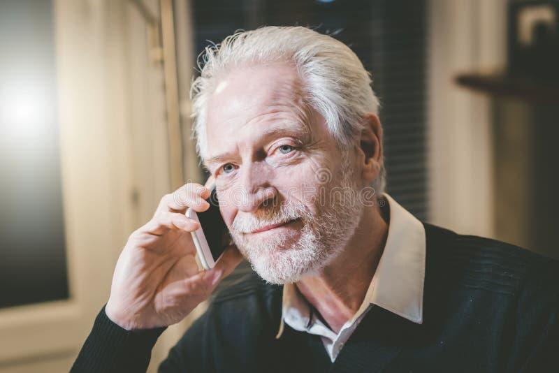 Stående av den höga moderna mannen som talar på mobiltelefonen arkivfoto