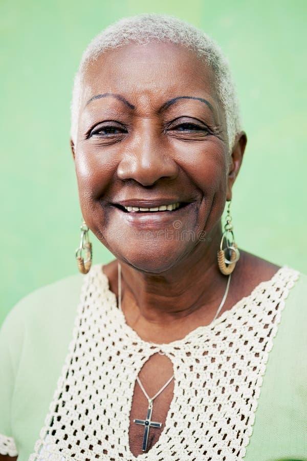 Stående av den höga svart kvinna som ler på kameran på grön backgr arkivbilder