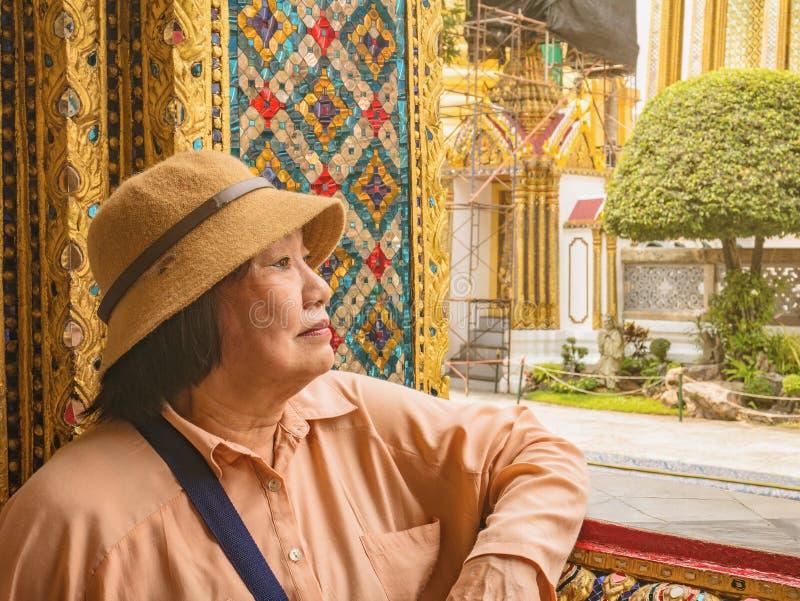 Stående av den höga turisten i Wat Phrakeaw Temple med molnhimmel Wat Phrakeaw Temple är den huvudsakliga templet av bangkok arkivfoton