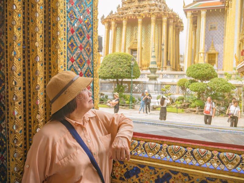 Stående av den höga turisten i Wat Phrakeaw Temple med molnhimmel royaltyfri foto