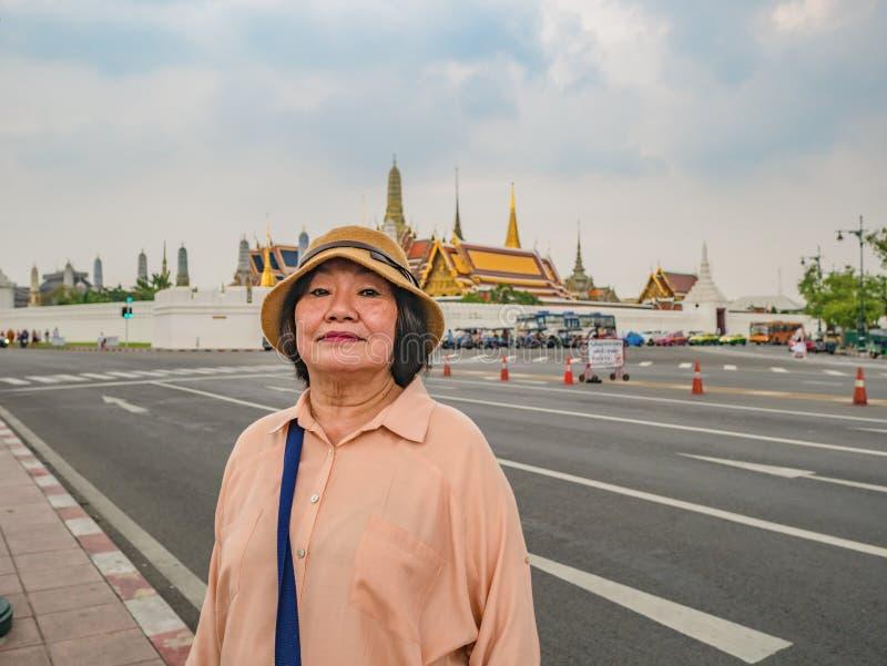 Stående av den höga turisten i Wat Phrakeaw Temple med molnhimmel Wat Phrakeaw Temple är den huvudsakliga templet av bangkok fotografering för bildbyråer