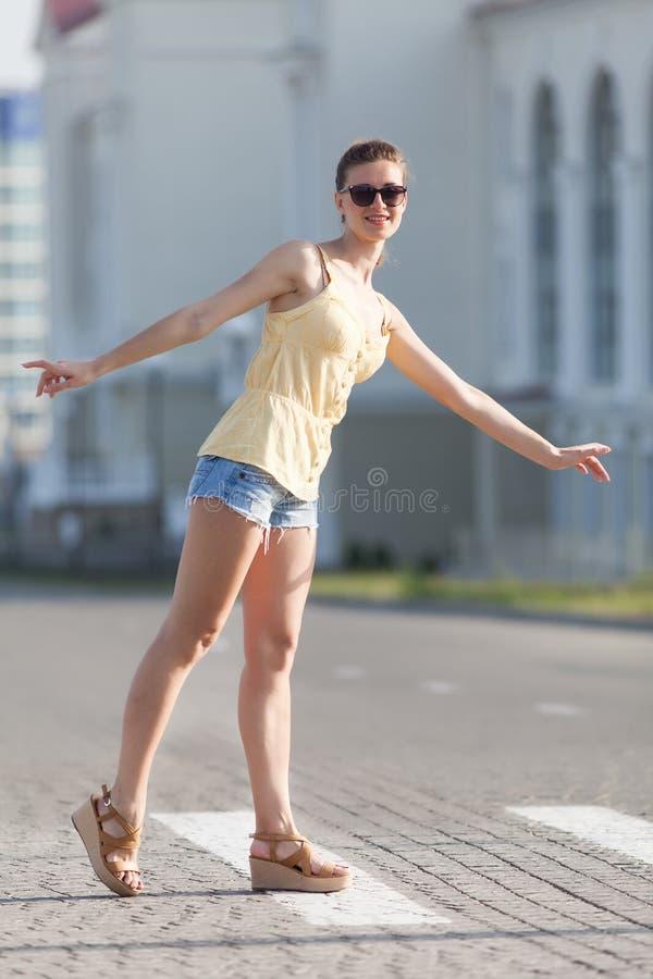 Stående av den högväxta kvinnan i gula sleeveless blus- och jeanskortslutningar på gatan royaltyfri foto