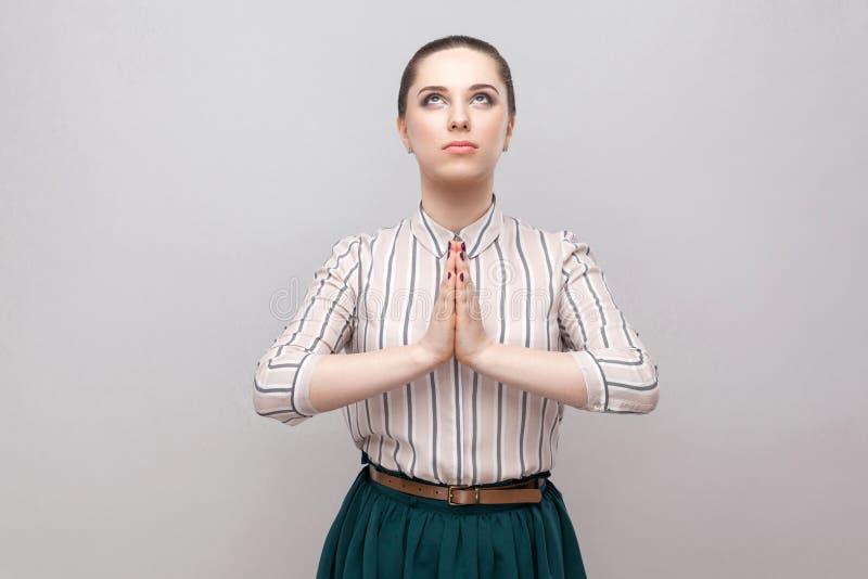 Stående av den hoppfulla härliga unga kvinnan i randig skjorta och grön kjol med makeup och den samlade förbudfrisyren som står, arkivfoton