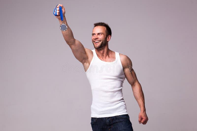 Stående av den idrotts- mannen i den vita undertröjan med mästaremedaljen fotografering för bildbyråer