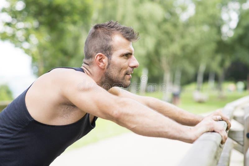 Stående av den idrotts- mannen som gör liggande armhävningar som är utomhus- arkivbild