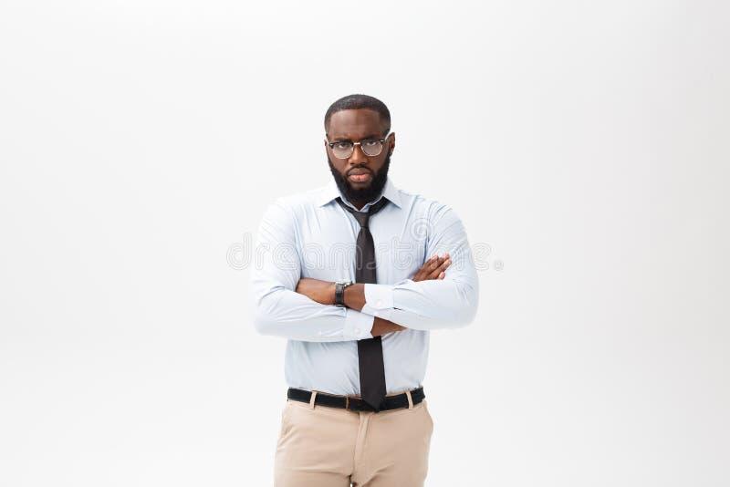 Stående av den ilskna eller förargade unga afrikansk amerikanmannen i den vita poloskjortan som ser kameran med misshagit royaltyfri foto