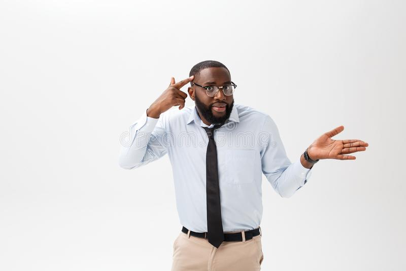 Stående av den ilskna eller förargade unga afrikansk amerikanmannen i den vita poloskjortan som ser kameran med misshagit arkivbilder