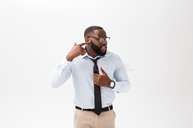 Stående av den ilskna eller förargade unga afrikansk amerikanmannen i den vita poloskjortan som ser kameran med misshagit royaltyfri bild