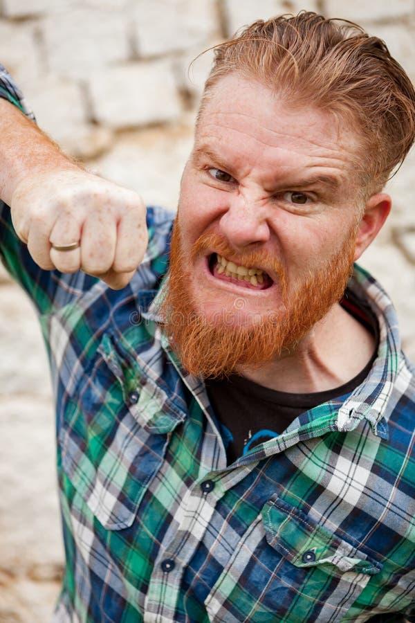 Stående av den ilskna röda haired hipstermannen med den blåa plädskjortan royaltyfri fotografi