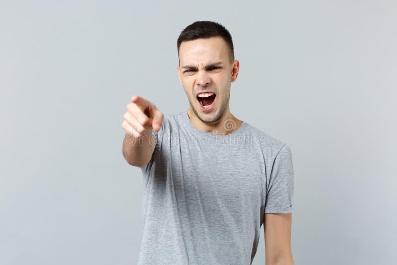 Stående av den ilskna skrikiga unga mannen i tillfällig kläder som svär som pekar pekfingret på kameran som isoleras på grå färge arkivbild