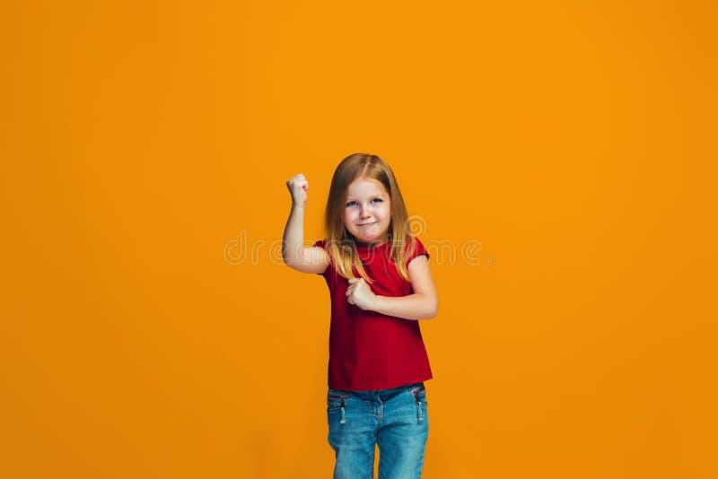 Stående av den ilskna tonåriga flickan på en orange studiobakgrund arkivfoto