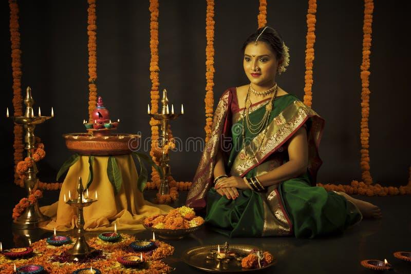 Stående av den indiska kvinnan som firar den Diwali festivalen, genom att tända lampan royaltyfria bilder