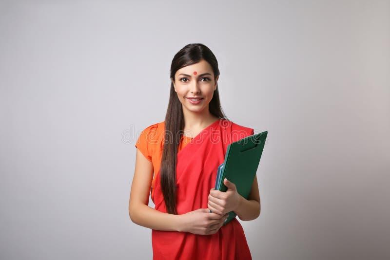 Stående av den indiska lärarinnan på ljus bakgrund arkivfoton