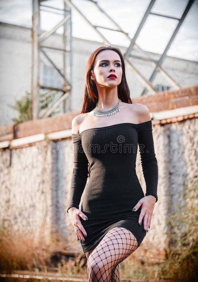 Stående av den informella modellen för härlig gothflicka i svart klänning och strumpbyxor som står i industriområde arkivbild