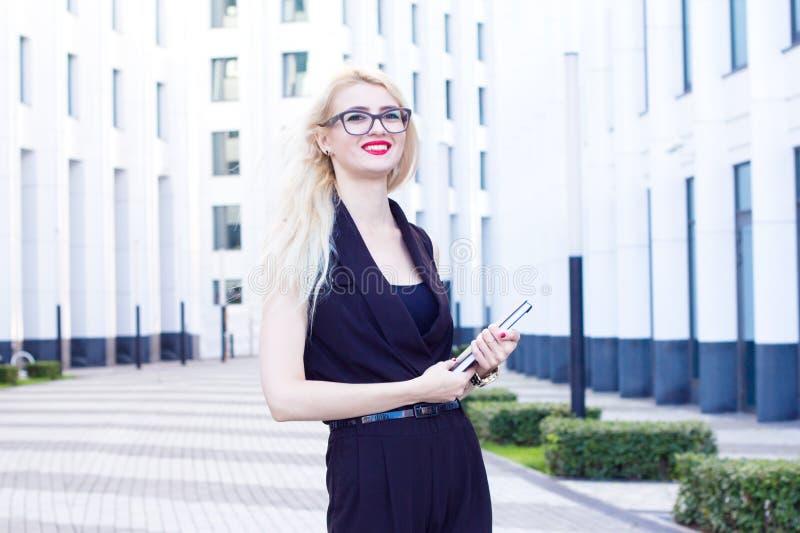Stående av den intelligenta blonda le kvinnan med en anteckningsbok på bakgrunden av affärsmitten arkivfoto