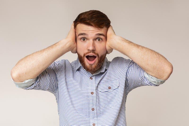 Stående av den irriterade mannen som ropar och täcker hans öron royaltyfria foton