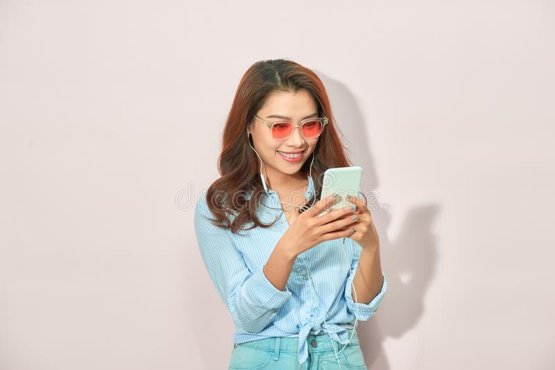 Stående av den kalla gladlynta flickan som har video-appell med vännen som rymmer den smarta telefonen som tycker om helgsemester arkivbilder