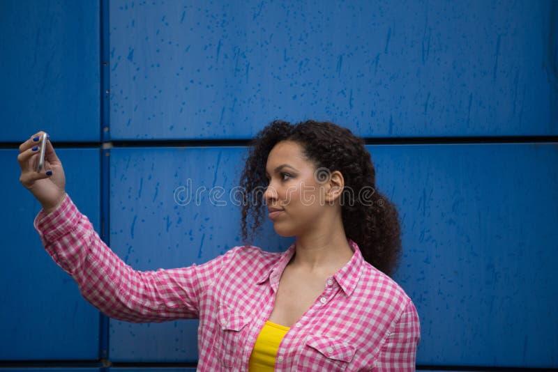 Stående av den kalla unga afrikansk amerikankvinnan som tar selfie arkivfoton