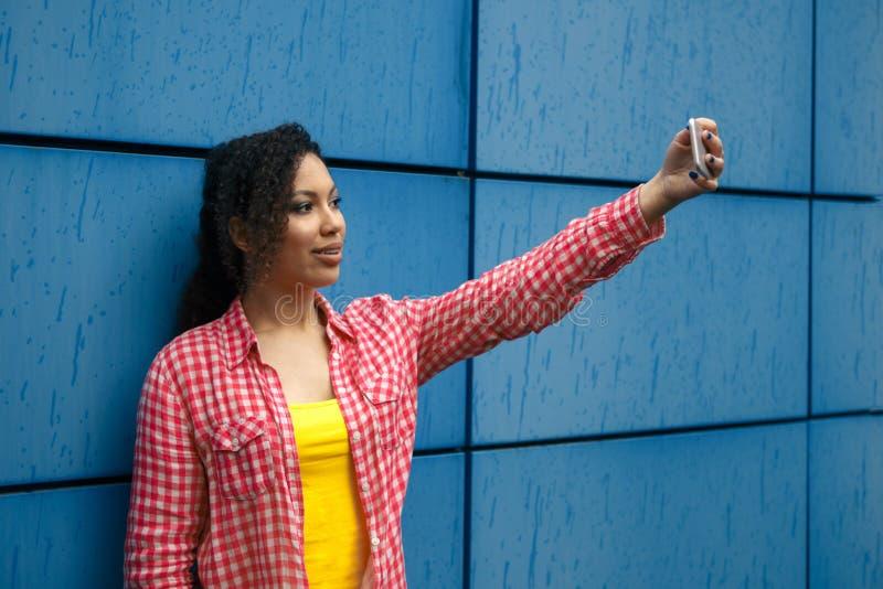 Stående av den kalla unga afrikansk amerikankvinnan som tar selfie royaltyfri foto