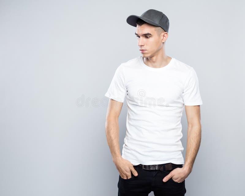 Stående av den kalla unga mannen i baseballmössa och vitt-skjorta royaltyfri bild