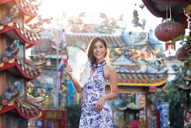 Stående av den kinesiska kvinnan att bära traditionell klänningcheongsam och rymmafanen på den kinesiska relikskrin i kinesiskt n arkivfoton