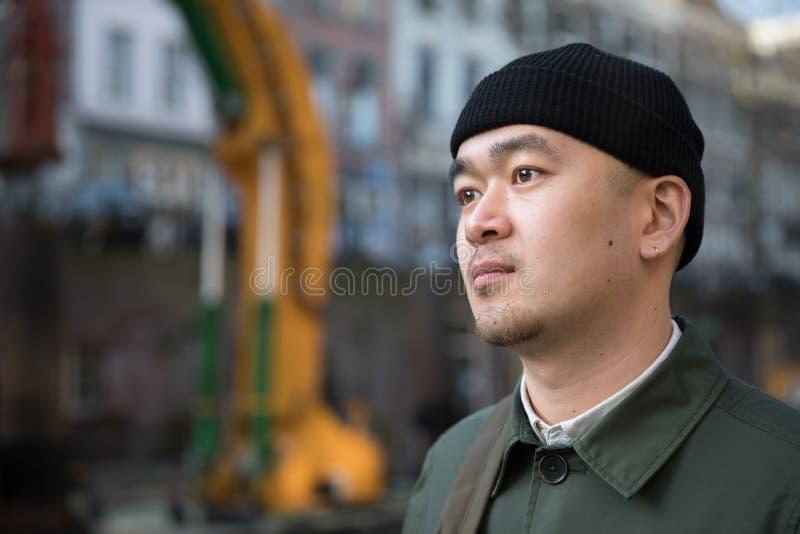 Stående av den kinesiska unga mannen mot stads- bakgrund royaltyfria bilder