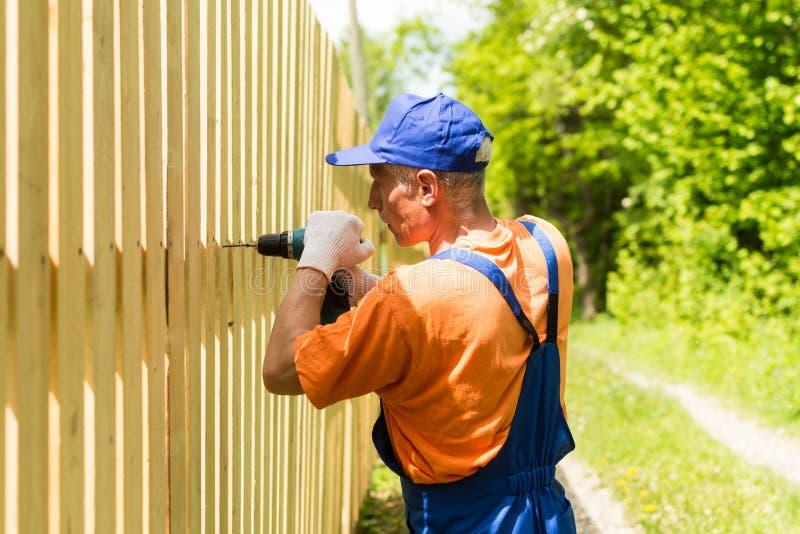 Stående av den kompetenta arbetaren som bygger trästaketet med sladdlös elektrisk skruvmejsel arkivfoton