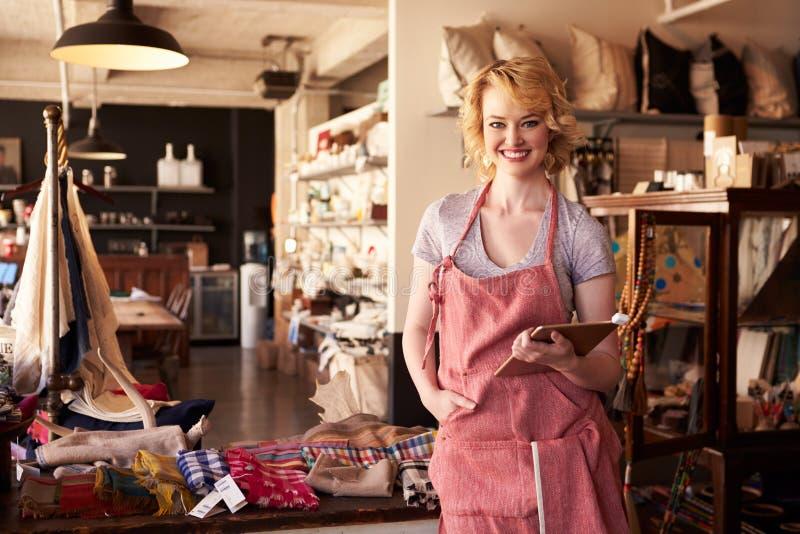 Stående av den kvinnliga ägaren av gåvalagret med den Digital minnestavlan arkivbilder