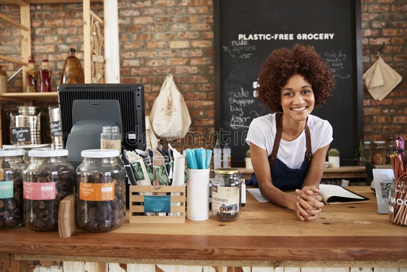 Stående av den kvinnliga ägaren av den hållbara plast- fria livsmedelsbutiken bak försäljningsskrivbordet arkivbild