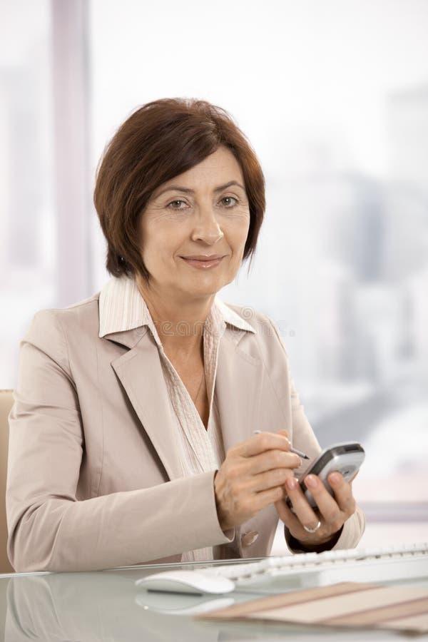 Stående av den kvinnliga affärskvinnan med smartphonen arkivfoton