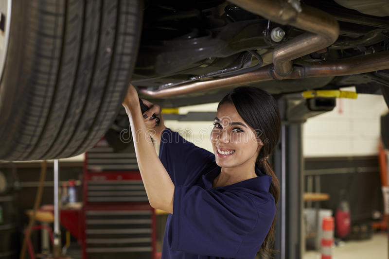 Stående av den kvinnliga auto mekanikern Working Underneath Car royaltyfri fotografi