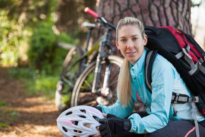 Stående av den kvinnliga bergcyklisten i skogen royaltyfria bilder