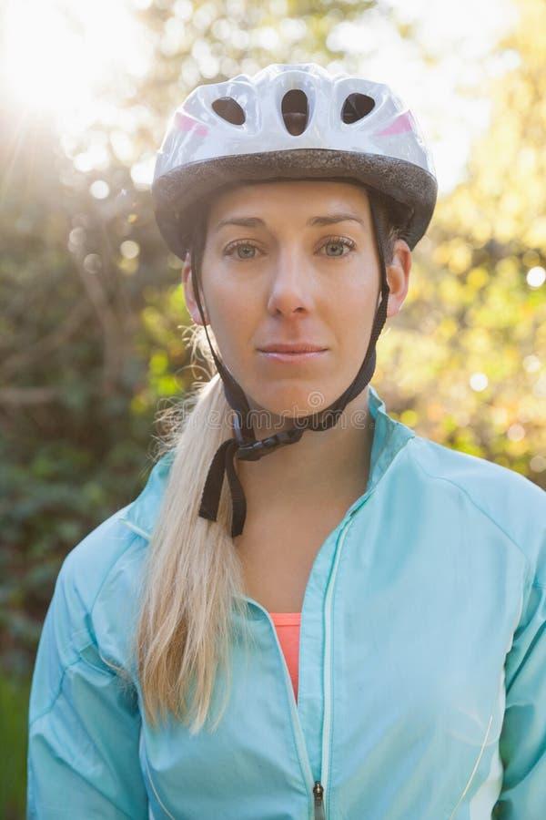 Stående av den kvinnliga bergcyklisten i skogen royaltyfri fotografi