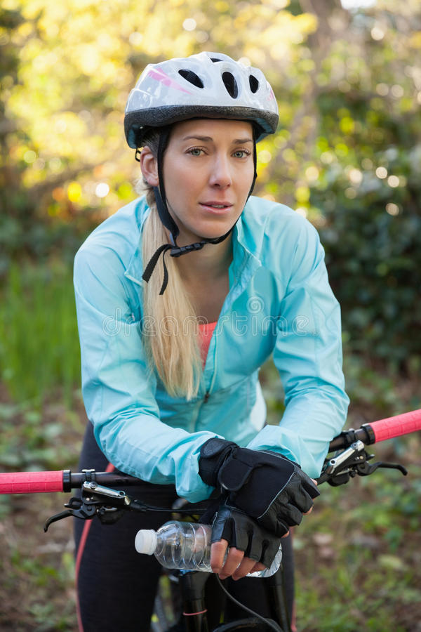 Stående av den kvinnliga bergcyklisten med cykeln royaltyfri foto