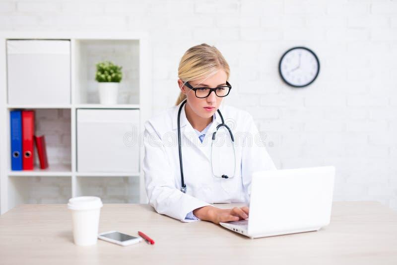Stående av den kvinnliga doktorn som i regeringsställning sitter och använder bärbara datorn royaltyfri foto