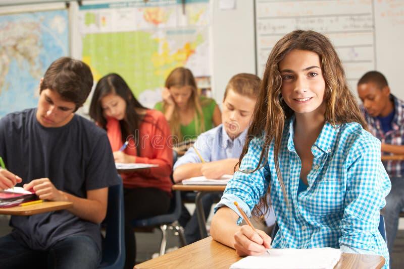 Stående av den kvinnliga eleven som studerar på skrivbordet i klassrum arkivfoto