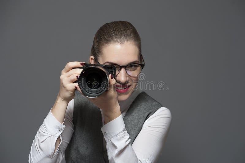 Stående av den kvinnliga fotografen med en kamera arkivfoton