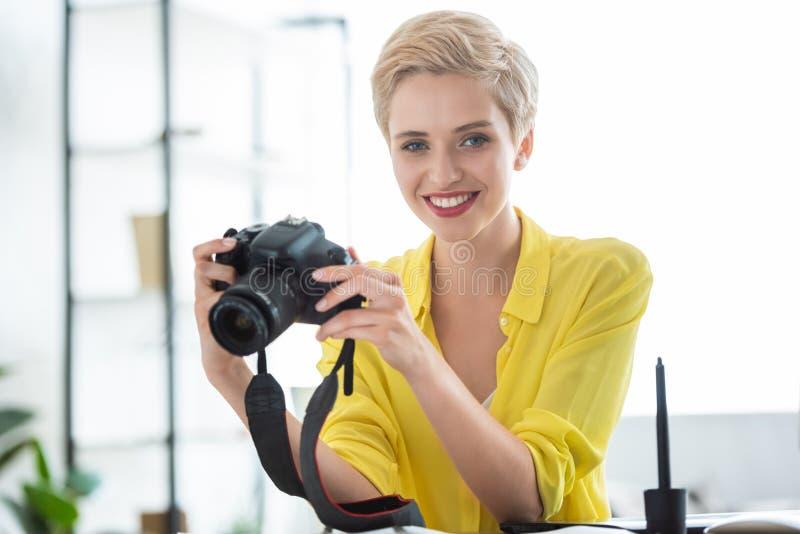 stående av den kvinnliga fotografinnehavkameran på tabellen royaltyfri bild