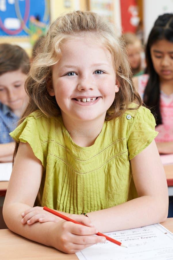 Stående av den kvinnliga grundskolaeleven som arbetar på skrivbordet arkivfoto