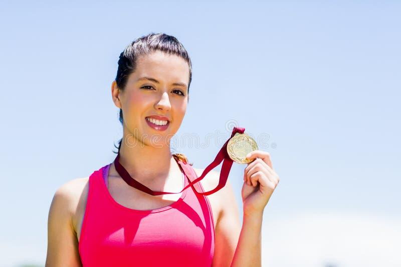 Stående av den kvinnliga idrottsman nen som visar hennes guldmedalj royaltyfri fotografi