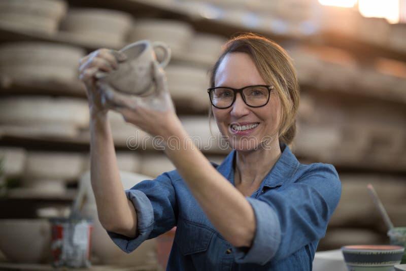 Stående av den kvinnliga keramikerdanandekoppen arkivfoto