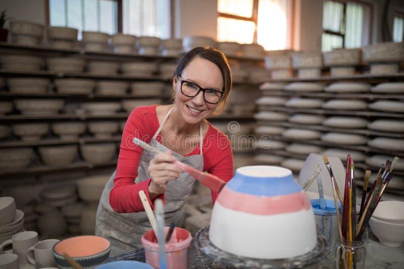Stående av den kvinnliga keramikermålningbunken arkivfoton