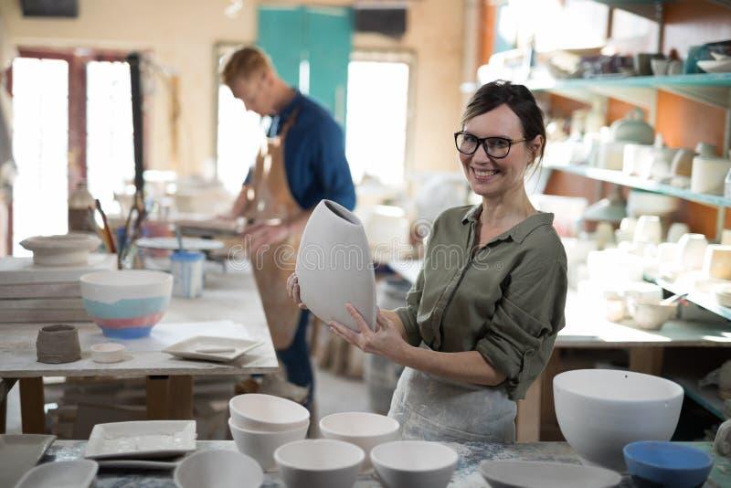 Stående av den kvinnliga keramikern som kontrollerar hantverkprodukten royaltyfri fotografi