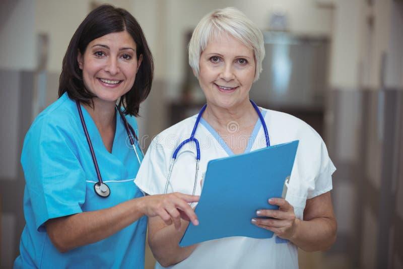 Stående av den kvinnliga kirurgen och sjuksköterskan som har diskussion på mapp royaltyfria foton